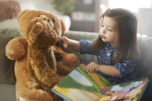 little-girl-reading-to-bear